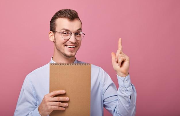 Довольно улыбающийся крутой парень в нежно-синей рубашке держит коричневую тетрадь и показывает