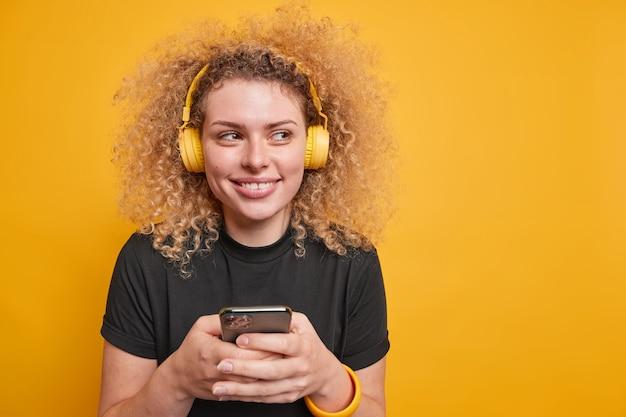 Довольно улыбающаяся кудрявая молодая женщина смотрит в сторону, счастливо слушает музыку, использует смартфон, хорошее качество звука, носит повседневную черную футболку, изолированную над желтой стеной с пустым пространством