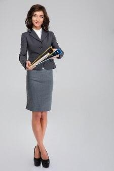 Довольно улыбающаяся кудрявая молодая деловая женщина в сером костюме стоит и держит папки с документами