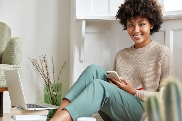 Довольно улыбающийся темнокожий студент колледжа беззаботно выглядит, одет в повседневную одежду, сидит на полу