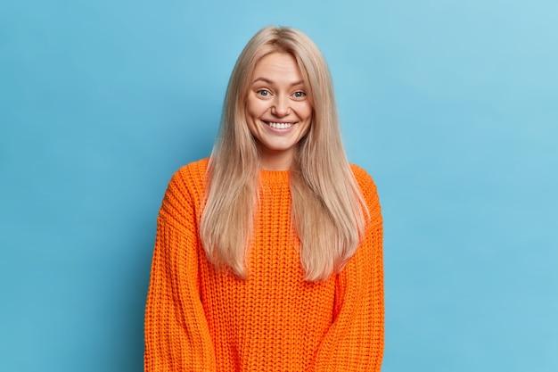 La donna europea abbastanza sorridente con un'espressione felice guarda felicemente, ha un sorriso a trentadue denti