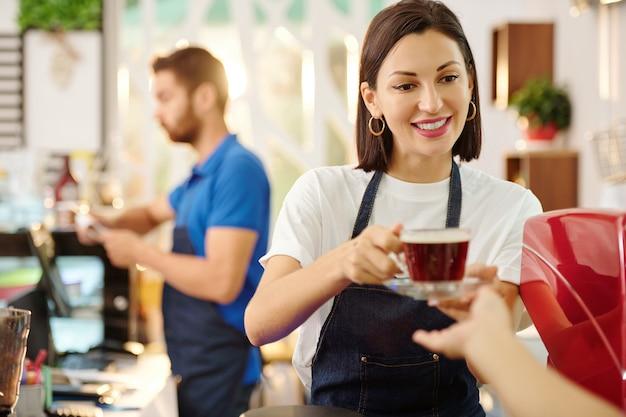 Довольно улыбается женщина-бариста, дающая клиенту чашку свежего кофе