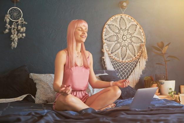 꽤 웃는 여성 모델은 짙은 파란색 벽으로 큰 침대에 있는 노트북 근처에서 명상합니다