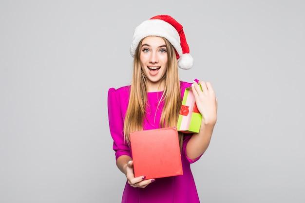 La signora felice divertente abbastanza sorridente in vestito rosa e cappello del nuovo anno tiene la sorpresa della scatola di carta nelle sue mani