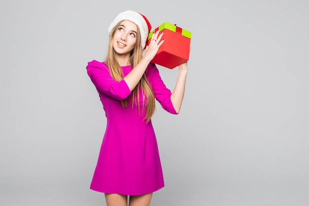 La signora felice divertente abbastanza sorridente in breve vestito rosa e cappello del nuovo anno tiene la scatola di carta nelle sue mani