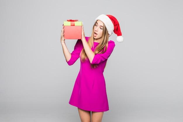 La signora felice divertente abbastanza sorridente in breve vestito rosa e cappello del nuovo anno tiene la sorpresa della scatola di carta nelle sue mani