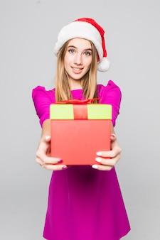 La signora divertente abbastanza sorridente in breve vestito rosa e cappello del nuovo anno tiene la sorpresa della scatola di carta nelle sue mani