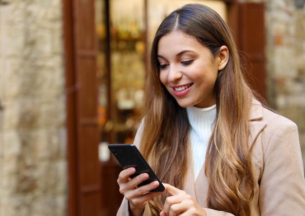 かなり笑顔の女の子が冬に通りを歩いてスマートフォンでオンラインで購入します。