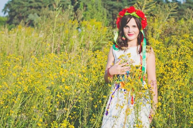 Милая улыбающаяся девушка в гирлянде из цветов мака и национального вышитого этнического платья позирует на лугу из желтых полевых цветов, освещенных летним солнцем