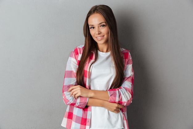 Довольно улыбается девушка в клетчатой рубашке, стоя с сложив