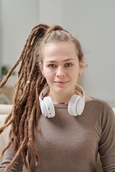 Довольно улыбающаяся девушка в пуловере с наушниками на шее, сидя перед камерой во время домашнего отдыха