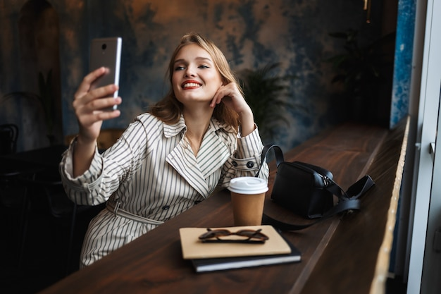 Pretty smiling girl in striped trench coat joyfully taking photos on cellphone with little black handbag and coffee to go near while spending time in modern cafe