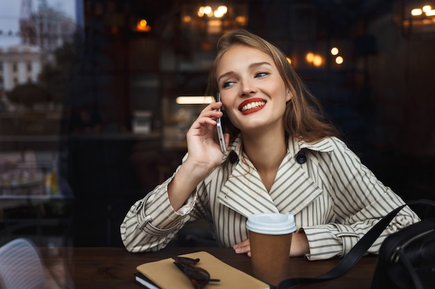 Pretty smiling girl in striped trench coat talking on cellphone joyfully