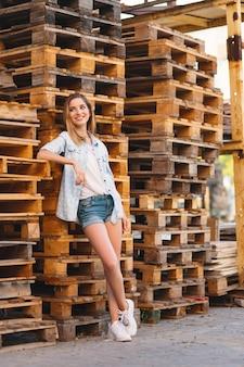 Милая улыбающаяся девушка в джинсах, шортах и рубашке позирует
