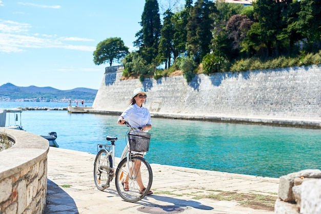 Pretty smiling girl with backpack standing with bicycle on sidewalk by sheltered harbor of resort town with high stone walls. perfect summer resort landscape. active lifestyle concept.