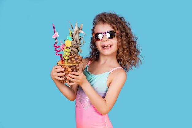 Милая улыбающаяся девушка с вьющимися волосами в розовых и голубых купальниках, в темных очках и с ананасовым коктейлем