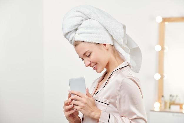 何かを撮影しながら自分の前にスマートフォンを持って頭にタオルでかわいい笑顔の女の子