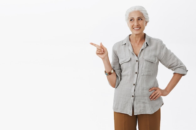 왼쪽 손가락을 가리키고 광고를 보여주는 꽤 웃는 할머니