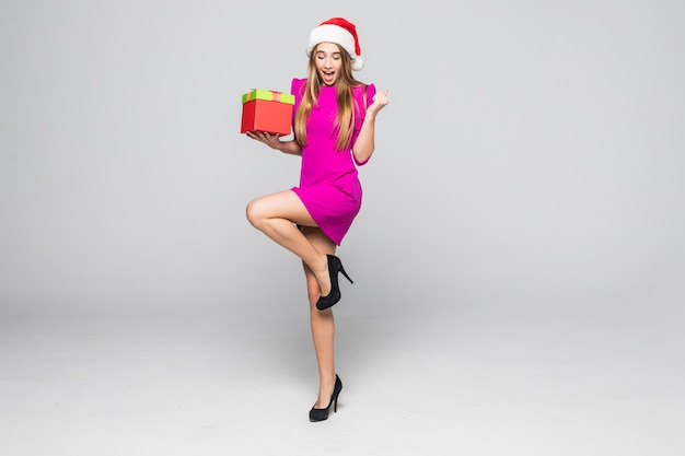 Pretty smiling happy lady in short pink dress and new year hat hold paper box surprise in her hands