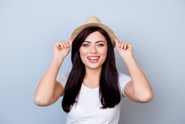 灰色の空間に対して彼女の帽子に触れてtシャツでかなり笑顔の幸せな女性