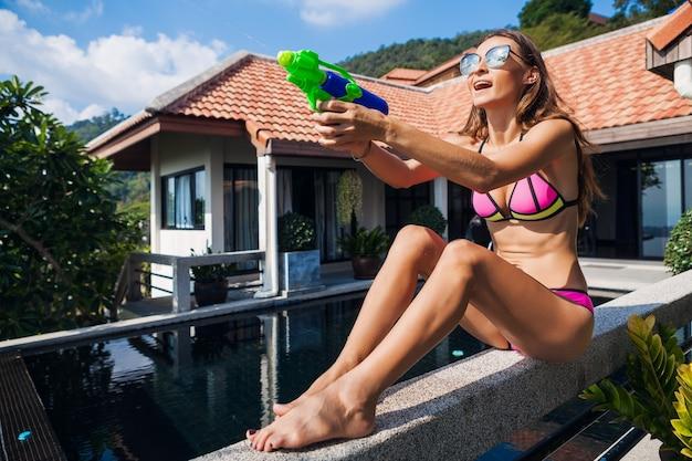 Donna felice abbastanza sorridente che gioca con il giocattolo pistola ad acqua in piscina in vacanza tropicale estiva in hotel villa divertendosi in costume da bagno bikini, stile colorato, atmosfera di festa