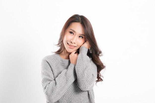 完璧な肌を持つ幸せなアジアの女性の肖像画を嬉しそうに笑ってかなり