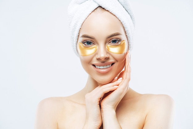 Pretty smiling lady has towel on head touches cheeks, applies golden hydrogel patches, stands shirtless indoor, removes wrinkles, isolated on white wall, has healthy fresh facial skin.