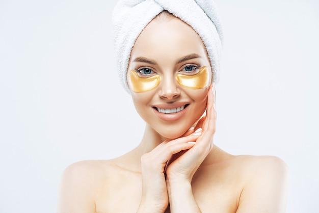 Симпатичная улыбающаяся дама с полотенцем на голове трогает щеки, накладывает золотые гидрогелевые пластыри, стоит в помещении без рубашки, разглаживает морщины, изолирована на белой стене, имеет здоровую свежую кожу лица.