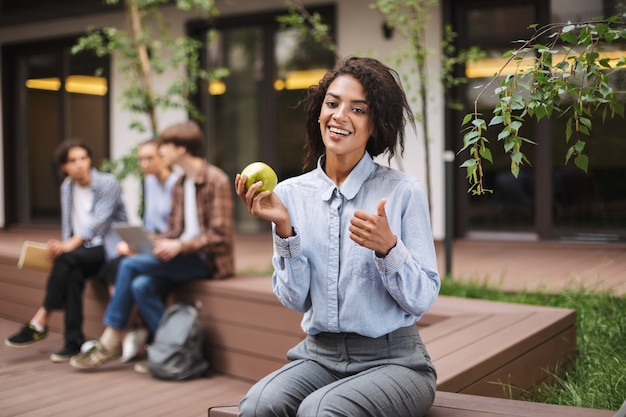 Pretty smiling lady sitting on bench with green apple and happily showing big thumb up gesture while