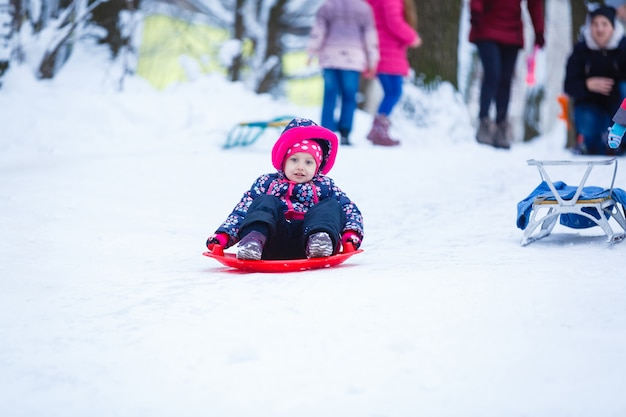 Pretty smiling little girl in her ski suit sliding down a small snow covered hill