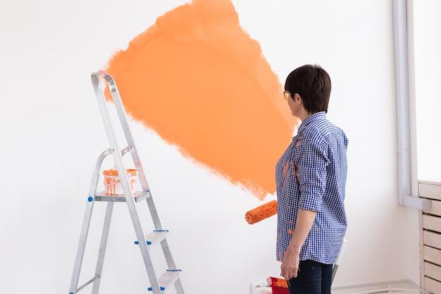 ペイントローラーで家の内壁を塗るかわいい笑顔の中年女性。