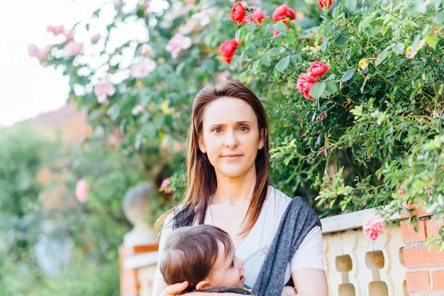 彼女の1歳の赤ちゃんを運ぶかなり笑顔のミレニアル世代の母親