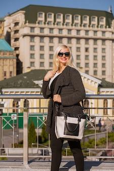회색 니트 코트를 입고 걷고 있는 예쁜 웃는 모델, 선글라스를 끼고 가죽 지갑을 손에 들고