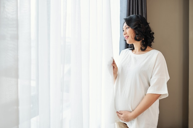 Pretty smiling pregnant young asian woman opening curtains and looking through window on the street