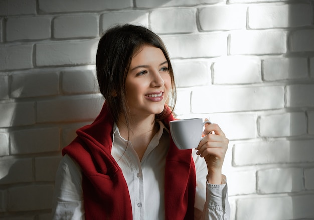 Pretty smiling student drinking coffee in the morning. having short black hair and light day make up. wearing casual white shirt and red cardigan. feeling good, happy.