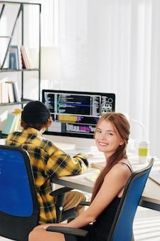 彼女の兄弟が自分の部屋の机でプログラミングしているときにカメラを見てかなり笑顔の10代の少女