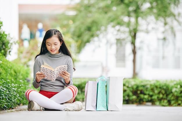Довольно улыбающаяся девочка-подросток сидит на тротуаре рядом с сумками и читает книгу