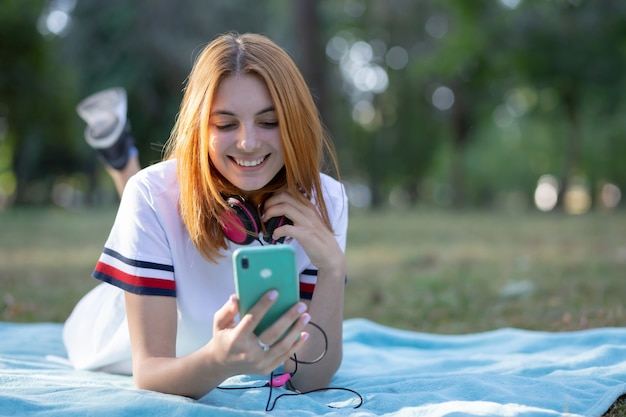 Pretty smiling teenage girl with red hair using sellphone outdoors in park.