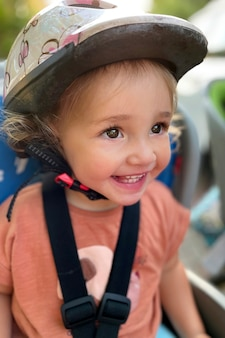 안전 헬멧을 쓰고 꽤 웃는 유아. 소녀는 자전거 아기에 앉아 있다. 세로 형식