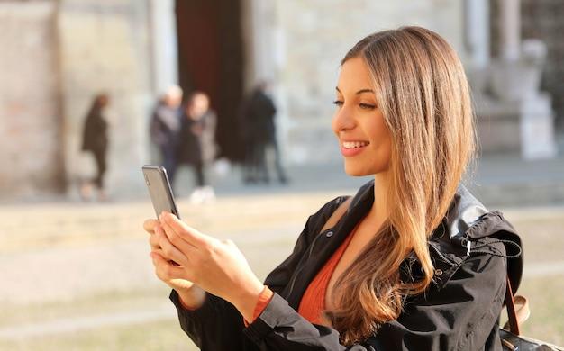 かなり笑顔の観光客の女の子がヨーロッパの芸術都市でスマートフォンでセルフポートレートを取る