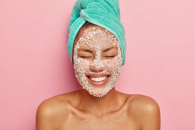 Pretty smiling woman applies salt granules on face, keeps eyes closed, shows white perfect teeth, wears turquoise towel, poses shirtless against pink wall