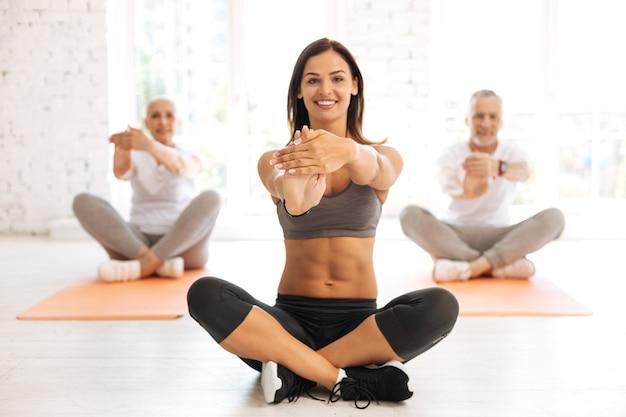 Довольно улыбается женщина скрещивает ноги и держит спину прямо, делая упражнения на растяжку