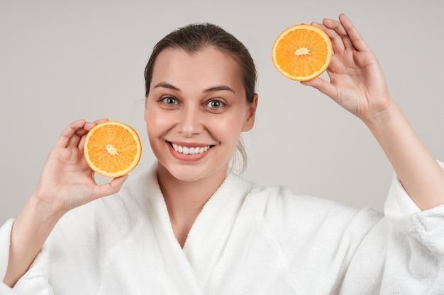 かなり笑顔の女性は彼女の手にオレンジの半分を持っています