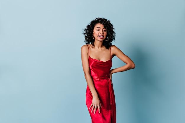 Довольно улыбается женщина в красном платье, глядя на фронт