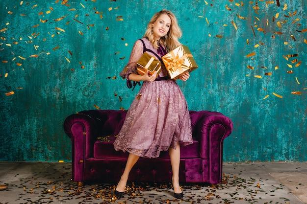 선물 벨벳 소파에 대한 세련된 보라색 이브닝 드레스에 예쁜 웃는 여자