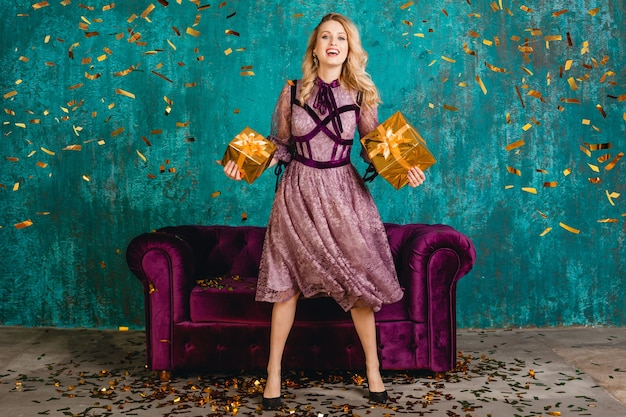 ギフトとベルベットのソファに対してスタイリッシュな紫のイブニングドレスでかなり笑顔の女性