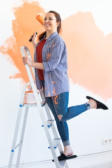 Pretty smiling woman painting interior wall of home with paint roller