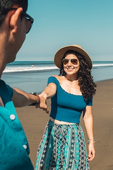 Pretty smiling woman pulling man to beach