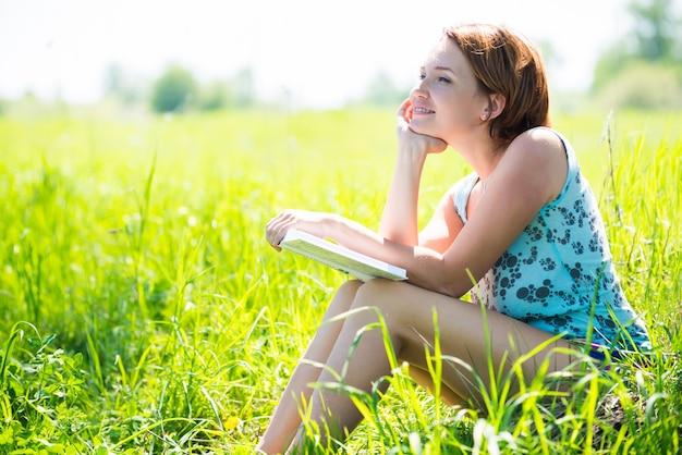La donna abbastanza sorridente legge il libro in natura