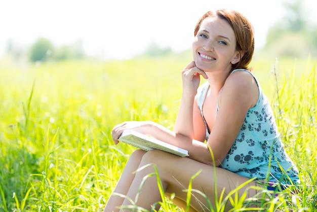 La donna abbastanza sorridente legge il libro alla natura